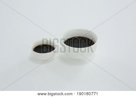 Close-up of two soy sauce bowl on white background