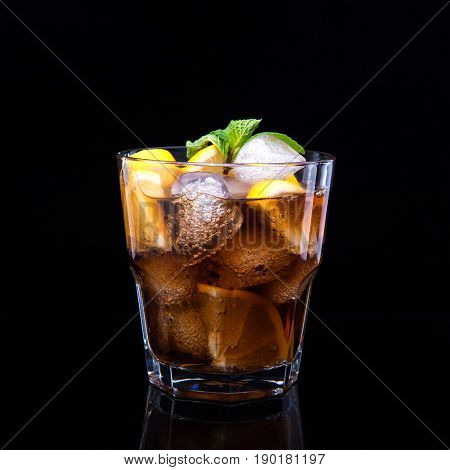 Glass of cola with ice, mint and lemon on black background.