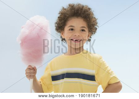 Mixed race boy eating cotton candy