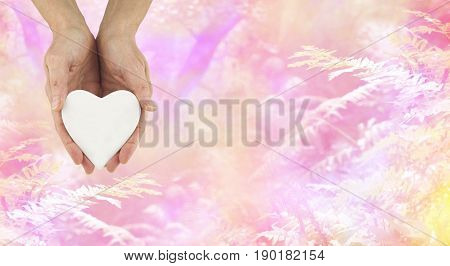 Love Nature - female hands holding a white ceramic heart shaped plaque against a beautiful romantic pink fern and trees background with copy space