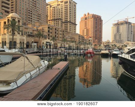 Harbour view at the Pearl in Doha, Qatar, with yachts, boats and buildings in the background. The Pearl is an artificial island with residential buildings, shopping centers etc