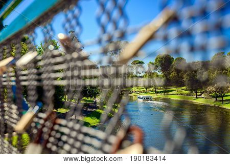Adelaide Australia - April 14 2017: Tourists boat in Adelaide CBD moving upstream in Torrens river on a bright day. Vewed through the guardrails of Adelaide University Bridge