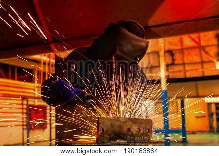 Industrial worker is welding with protective mask in factory