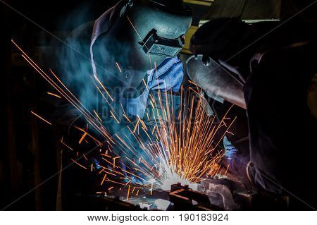 workers are welding assembly car parts in automotive industrial factory with protection mask