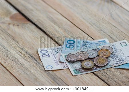 Different Polish Zloty On The Old Wooden Background