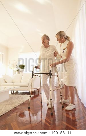 Older Caucasian woman and caregiver using walker