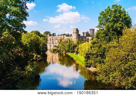 Warwick UK. Castle of Warwick from outside with reflection in a river. It is a medieval castle built in eleventh century and a major touristic attraction in UK nowadays. Sunny day cloudy sky