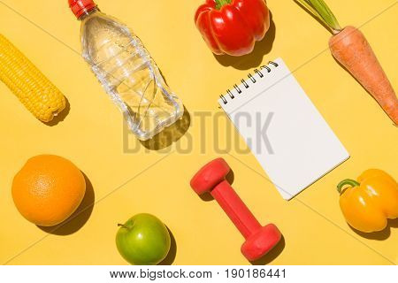 Fitness Concept. Collection Of Fresh Fruits With Dumbells And Water Bottle On Yellow Background.