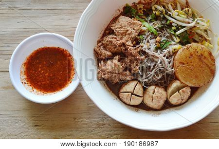 rice vermicelli topping pork ball and meat in brown soup with spicy sauce