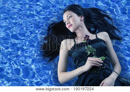 Pacific Islander woman in black gown floating on water