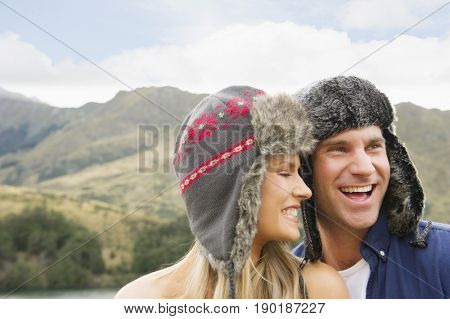Caucasian couple laughing in rural landscape