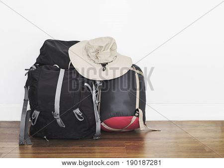 Backpack with sleeping bag and adventure hat, on wooden floor with white wall, adventurous preparation
