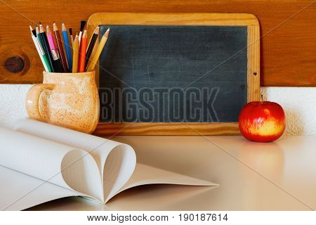 Teacher's or knowledge day concept: a blackboard a red apple pencils and a textbook with pages in a heart form