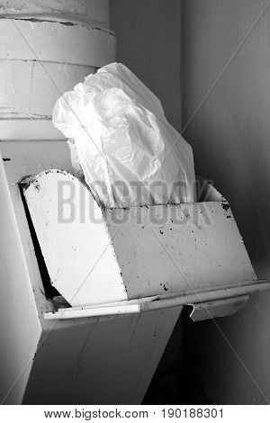 A jammed cellophane bag stuck in disposal bin vertical image in black and white