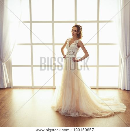 Beautiful young girl bride with fashion wedding hairstyle . Portrait of a young gorgeous bride in wedding white dress blue eyes . Wedding.