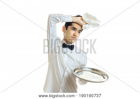 tired of the young waiter with tray put his hand with a napkin on his head isolated on white background