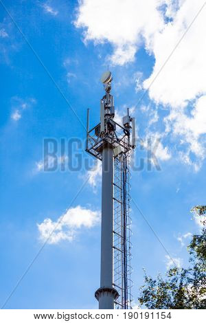 Cellular network mobile telephony radio tower against blue sky