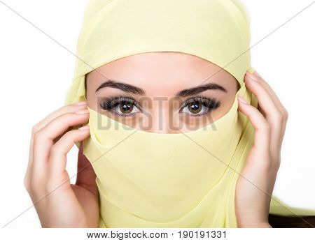 Closeup of beautiful young arabian woman in yellow hijab. Charm and beauty of the East