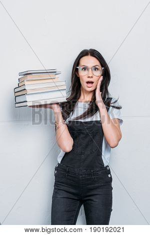 Astonished Caucasian Student Holding Books With Facial Expression