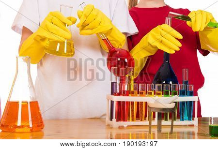 children doing chemistry science experiment with colorful reagents in school