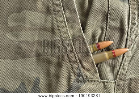 Two rifle bullets hidden into military camo pocket pants. Military ammunition