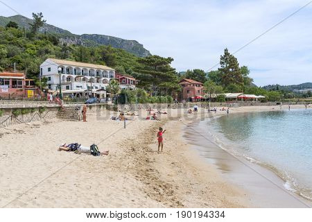 PALEOKASTRITSA, GREECE - MAY 15: Tourists enjoying the beautiful weather rest on the beach on May 15, 2017 in Paleokastritsa resort, Corfu island in Greece.
