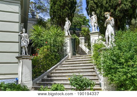 GASTOURI, GREECE - MAY 15: Classical inspired statues on stairs to the Achilleion palace on May 15, 2017 in Gastouri, Corfu island in Greece.