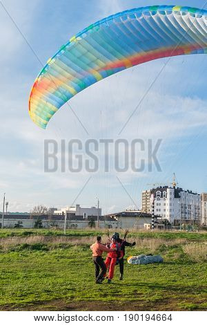 Landing a tandem paraglider on paradrome on a Sunny day.