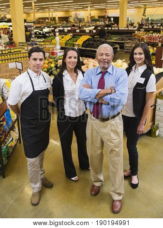 Businessman and workers smiling in grocery store