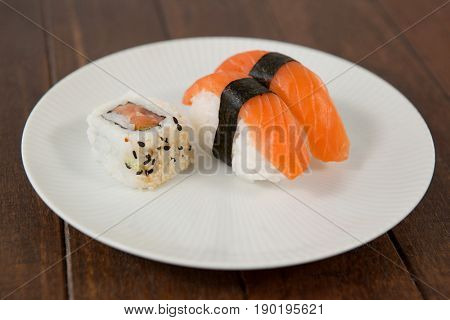 Nigiri and uramaki sushi served in white round plate on wooden table