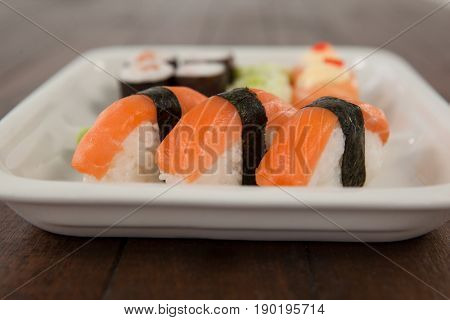 Three nigiri sushi served in white plate on wooden table