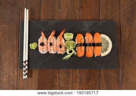 Nigiri sushi served with chopsticks in black stone slate