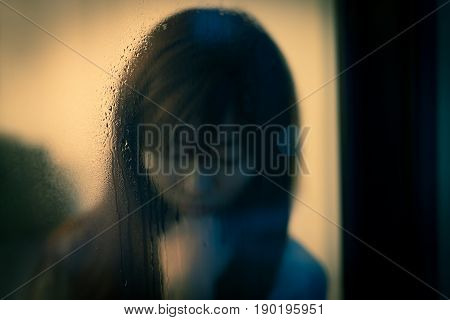 woman feel depression next to the window