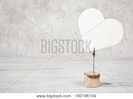 Blank heart shaped frame on wooden table against vintage wall