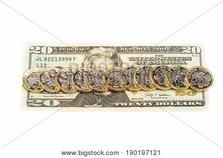 British one pound coins laid across 20 dollar bill