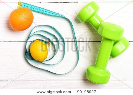 Lemon and orange fruit in circle made of cyan blue measuring tape near green lightweight dumbbells on white wooden background top view. Concept of vegetarian food for fitness and healthy shape