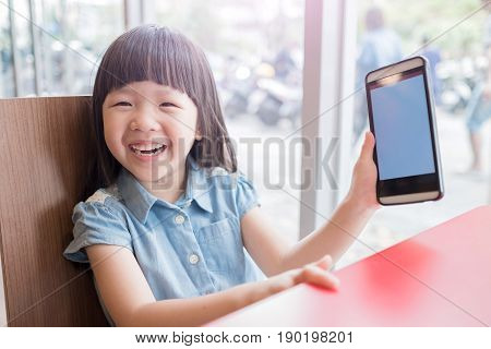 cute girl use phone in the resturant and show blank screen to you