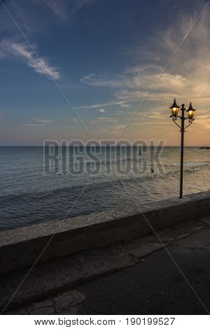 sea shore. empty embankment quay with lightened lanterrn at sunset sunrise. beautiful sea view at dusk dawn