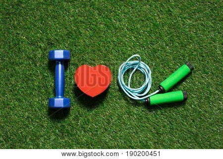 Colorful Dumbbell With Heart Symbol And Skipping Rope On The Grass