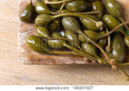 Canned Capers In Wooden Dish .