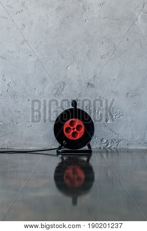 Round Extension Cord With Four Sockets Near Grey Wall Indoors