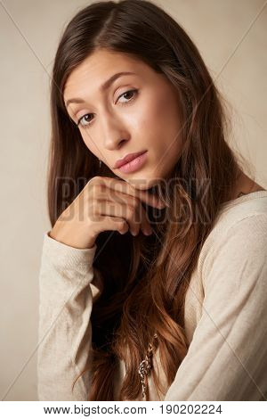 Attractive pensive woman with long healthy hair looking at camera