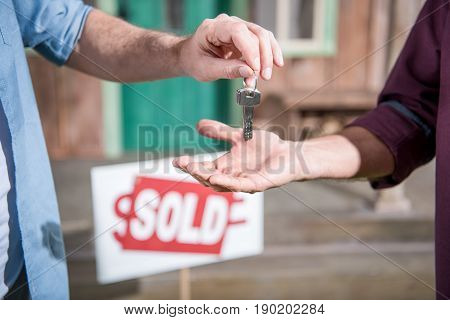Cropped View Of Man Buying New House And Taking Keys, Sold Sign Behind
