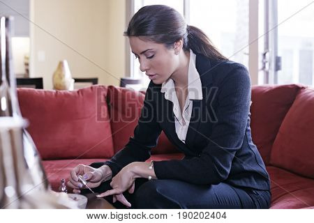 Mixed race businesswoman painting her nails