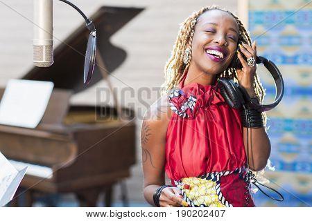 African American singer listening to track in studio