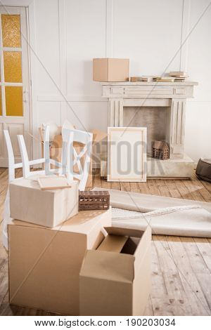 Cardboard Boxes And Furniture In Empty Room, Relocation Concept