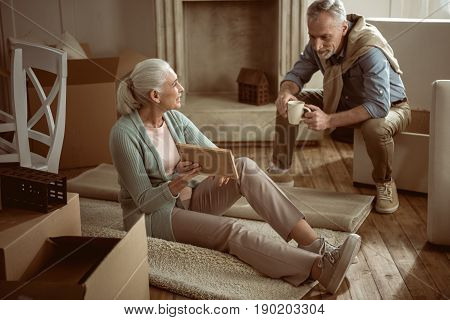 Senior Wife Showing Old Photo To Her Husband While Taking Break From Packing Cardboard Boxes, Moving