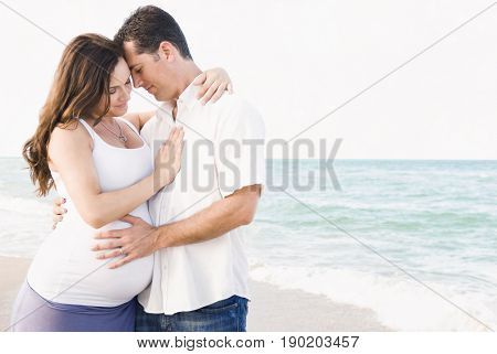 Caucasian man hugging pregnant wife on beach