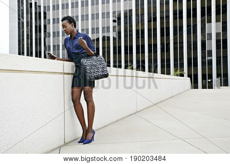 African American businesswoman using cell phone on city street
