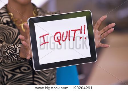 Mixed race businesswoman holding tablet computer that reads 'I quit!!'
